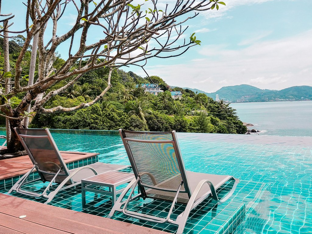 Two sun chairs and view of the infinity pool and the bay at U Zenmaya hotel in Phuket, Thailand