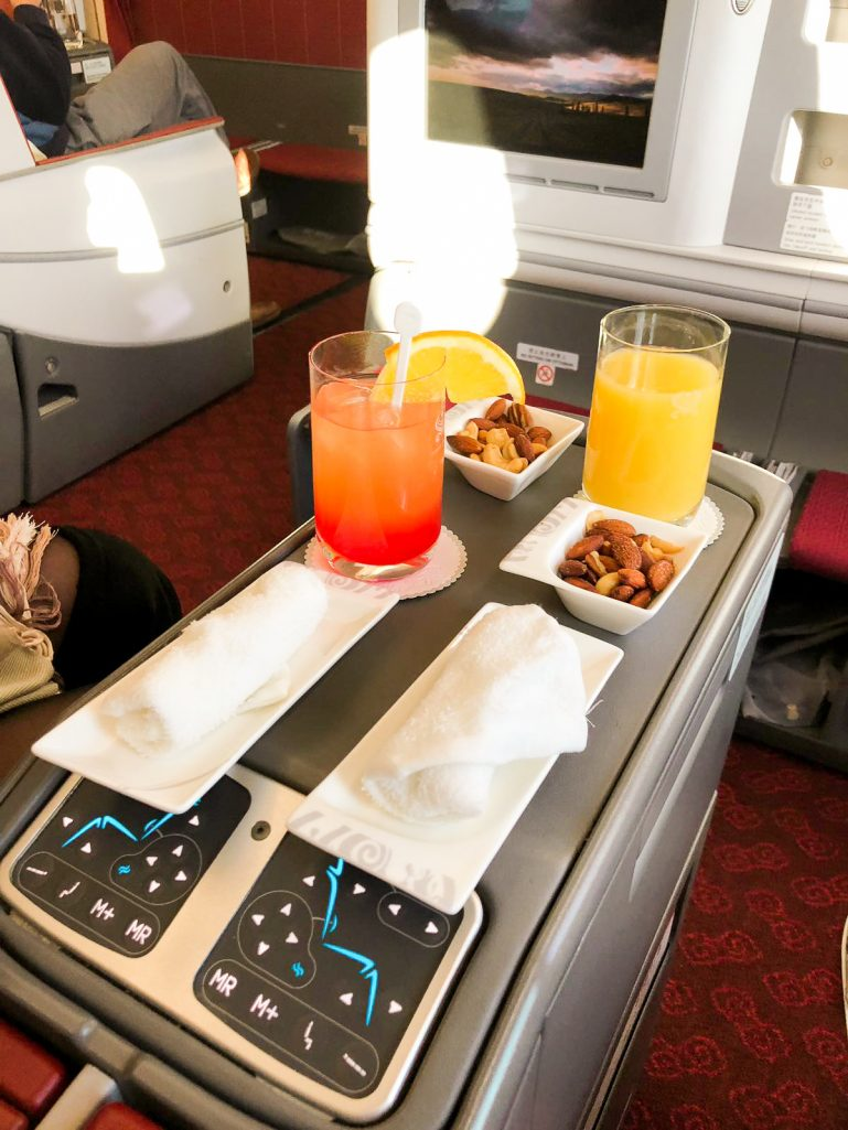 Welcome drinks and nuts on Hainan Airlines Business Class flight.